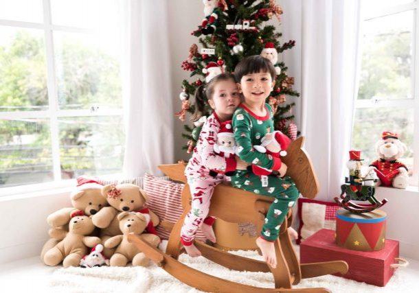 menino e menina em cima de cavalinho de madeira em ensaio de natal em família estúdio de fotografia laura alzueta pinheiros sp